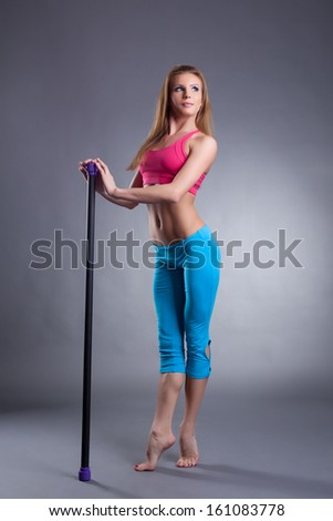 Pretty slim girl standing on tiptoe with fitbar - stock photo