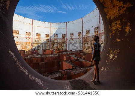 Pretty slim girl stands in rusty old abandoned factory at summer day, back view