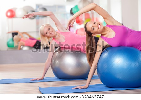 Pretty slim girls are doing exercise in fitness center. They are lying on balls and stretching arm sideways. The ladies are smiling and looking at camera happily