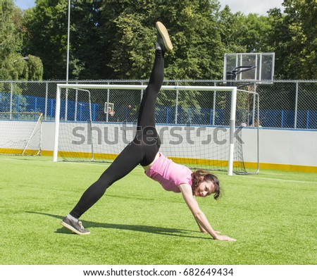 Pretty slim woman exercising on the stadium field, active lifestyle concept.