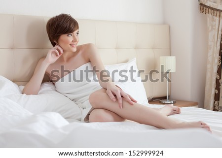 Pretty slim woman posing lying in bed, close-up - stock photo