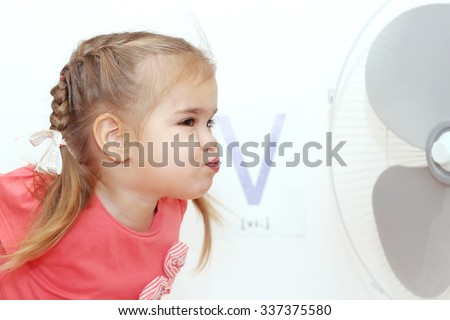 Pretty small girl blowing on the electric fan (ventilator) over white background with V letter on it, indoor portrait, ABC concept - stock photo