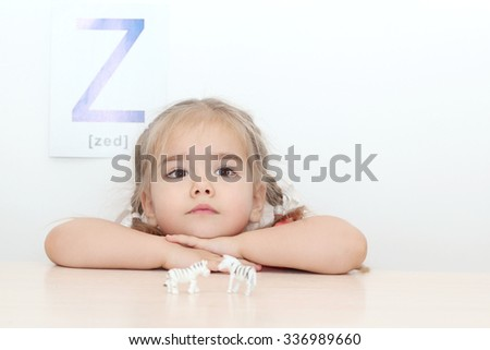 Pretty small girl dreaming near two tiny toy zebras over white background with Z letter on it, indoor portrait, ABC concept - stock photo