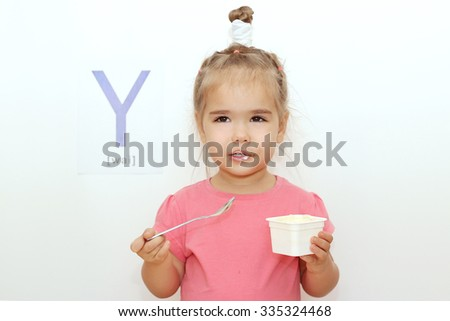 Pretty small girl eating a yogurt over white background with Y letter on it, indoor portrait - stock photo