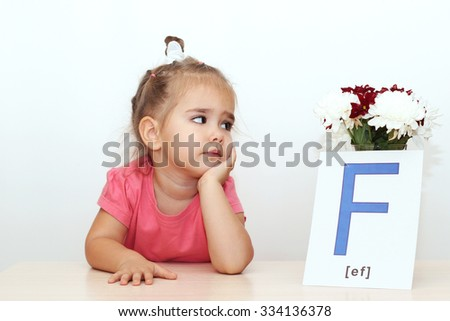 Pretty small girl looking on the bunch of flowers and picture with F letter over white background, indoor portrait - stock photo