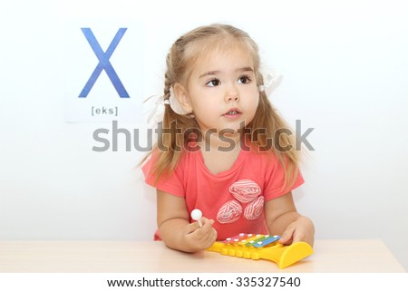 Pretty small girl playing on a xylophone over white background with X letter on it, indoor portrait - stock photo