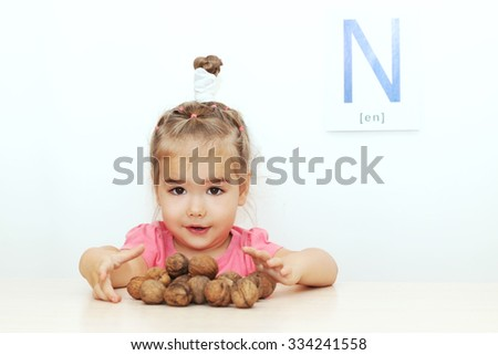 Pretty small girl scattering walnuts over white background with N letter on it, indoor portrait - stock photo