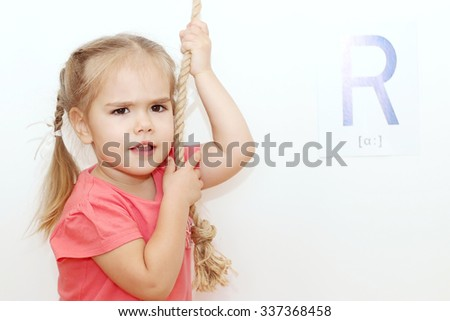 Pretty small girl with plaits pulling a rope over white background with R letter on it, indoor portrait, ABC concept - stock photo