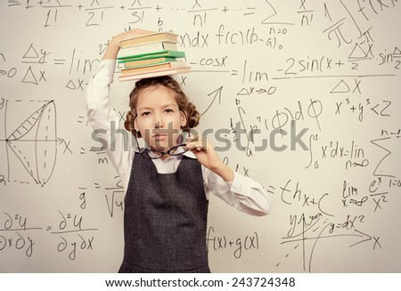 Pretty smart schoolgirl in big glasses stands with books at the blackboard. Education. - stock photo