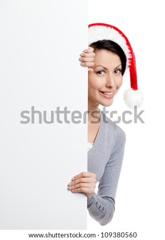 Pretty smiley woman peeps out through the wall, wearing Christmas red cap, isolated on white - stock photo