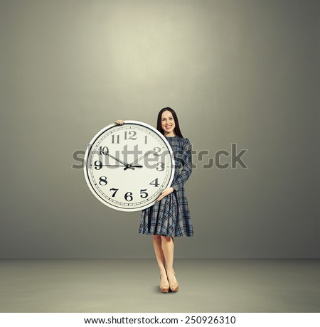 pretty smiley woman with big white clock over grey background - stock photo