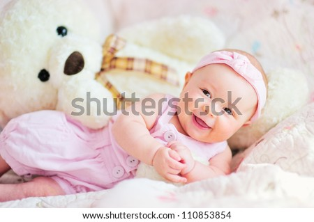 pretty smiling baby girl and teddy bear lying in the bed - stock photo