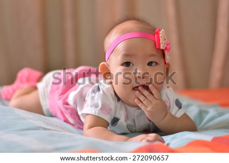 pretty smiling baby girl lying in the bed