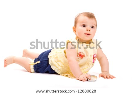 Pretty  smiling baby in suit from summer blouse and jeans shorts lying on belly and hold in hand a cap from child`s food jar