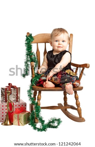 Pretty smiling baby in velvet embroidered patchwork dress sits in rocking chair with festive holiday gifts and garland. Vertical, isolated/cut out on white background, copy space.
