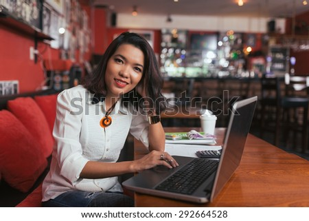 Pretty smiling bar owner working on laptop at the table - stock photo