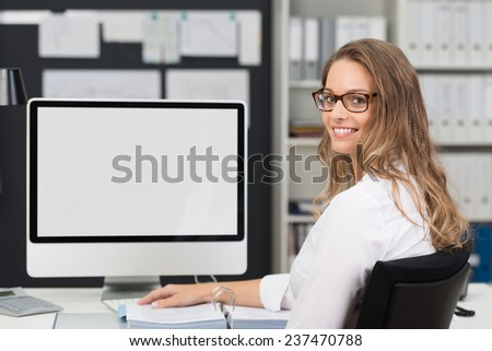 Pretty Smiling Blond Office Woman Sitting at her Worktable with Computer While Looking at the Camera. - stock photo