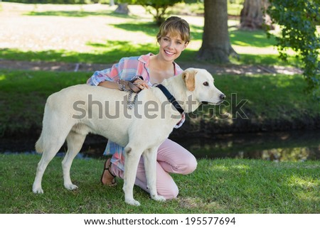 Pretty smiling blonde kneeling with her labrador in the park on a sunny day - stock photo