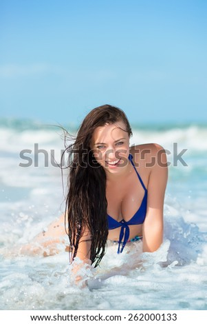 Pretty smiling brunette posing on the beach