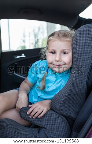 Pretty smiling child in car safety seat looking at camera - stock photo