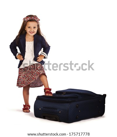 pretty smiling child next to a suitcase - stock photo