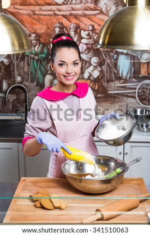 Pretty smiling confectioner, wearing in pink dress, apron and blue gloves, holding yellow scoop, and cooking in metallic bowls with dough and flour, on wooden board with rolling pin and gingerbread