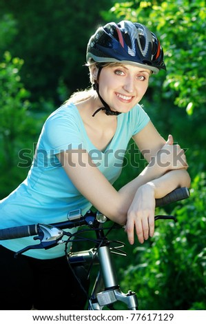 Pretty smiling cyclist girl with a  bottle of water