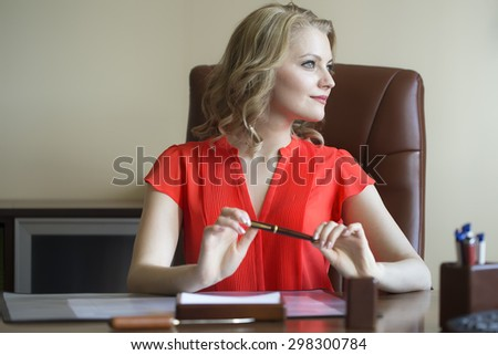 Pretty smiling elegant blond business woman sitting in office on brown leather chair in red blouse holding pen in hands looking away indoor on white background, horizontal picture - stock photo