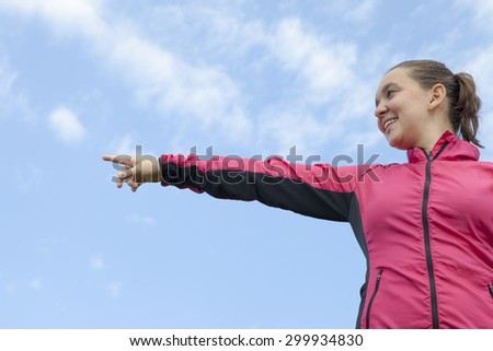 Pretty smiling female hiker showing, pointing on something, high in the mountains, against  blue sky, space for text