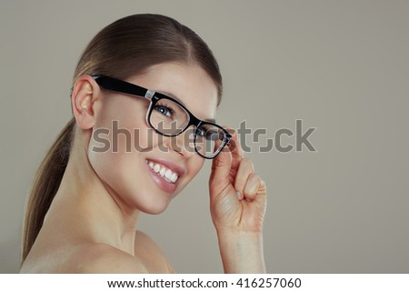 Pretty smiling female wearing stylish eyeglasses posing in studio. Concept of vision and ophthalmology.  - stock photo