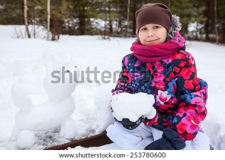 Pretty smiling girl at wintertime with snow dog sculpture - stock photo
