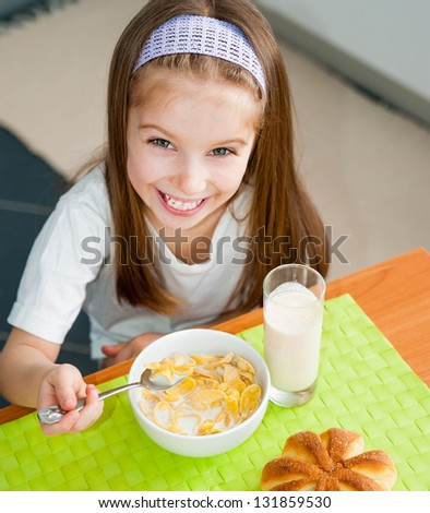 pretty smiling girl eating her breakfast in the kitchen - stock photo