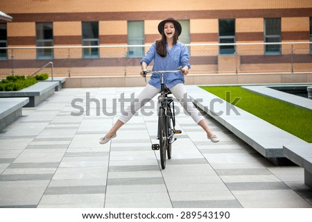 Pretty smiling girl in hat and blue dress riding a bicycle at street lifting legs - stock photo