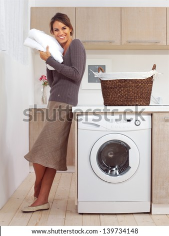 pretty smiling girl in the laundry room l - stock photo