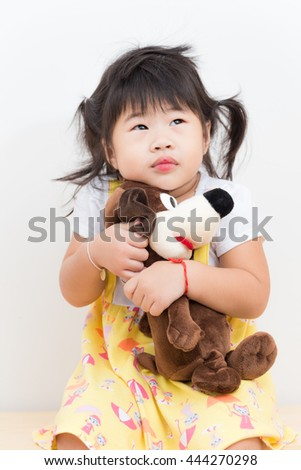 Pretty smiling girl playing with lovely dog doll on white background