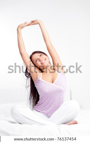 pretty smiling girl sitting on the bed at home waking up and stretching - stock photo