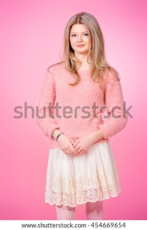 Pretty smiling girl with beautiful blonde long hair over pink background. Studio shot. - stock photo