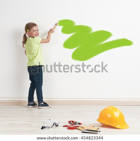 Pretty smiling girl with paintbrush coloring the wall with green stain. Concept of new realty and relocation.
