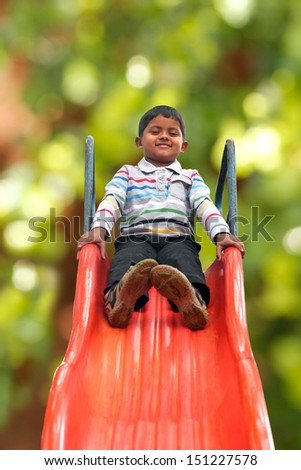 Pretty smiling indian boy ( kid ) on slider at a park. This boy's photo with green background & clipping path shows summer time playground with a schoolboy playing on a slider  - stock photo