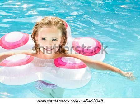 Pretty smiling little girl in swimming pool  - stock photo