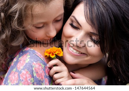 Pretty smiling mother and daughter - stock photo