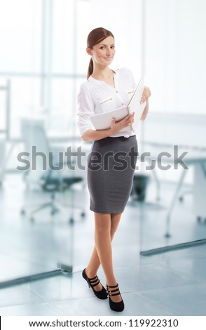 Pretty smiling office lady with open notebook in her hands, office background