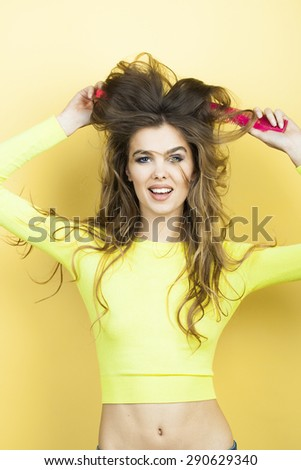 Pretty smiling playful young woman with long curly hair in yellow blouse and blue jeans holding two pink hair brushes standing on yellow background, vertical picture - stock photo