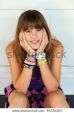 Pretty smiling teenage girl sitting in front of the white door on warm summer day. - stock photo
