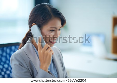 Pretty smiling Vietnamese business lady talking on the phone