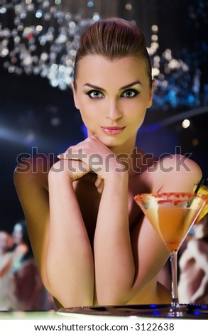pretty smiling woman drinking cocktail in nightclub, different kinds of lighting, shallow DOF - stock photo