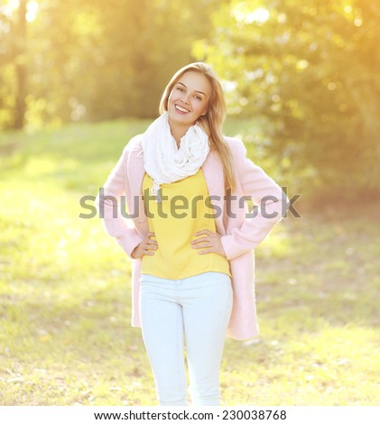Pretty smiling woman in coat outdoors sunny autumn day - stock photo