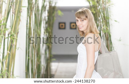 Pretty smiling woman in white dress and grey bag on her shoulder entering hotel hall. Entry decorated with high tropical plants or bamboo. Summer holidays and vacations. Hotels and resorts. - stock photo