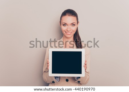 Pretty smiling woman showing black screen of digital tablet - stock photo