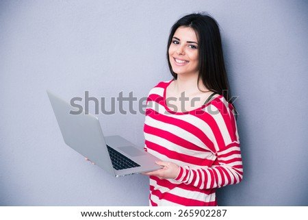 Pretty smiling woman standing with laptop over gray background. Looking at camera